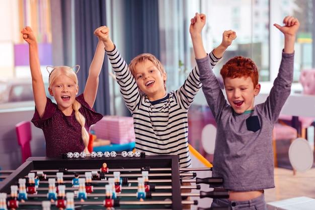 Nasza wygrana. pozytywnie zachwycony rudowłosy chłopak z uśmiechem na twarzy i stojącym obok znajomych