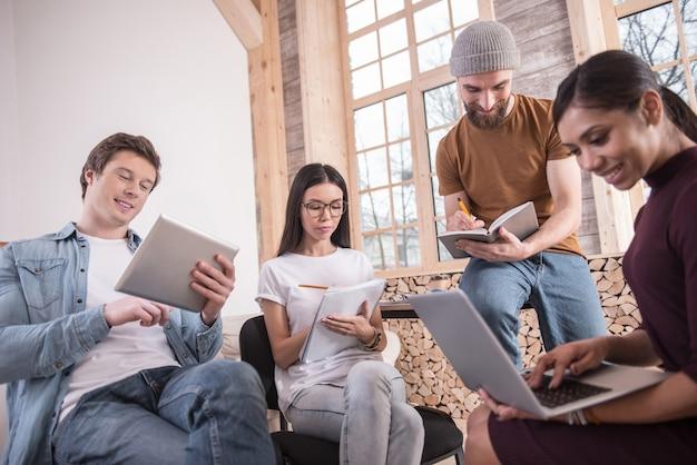 Nasze obowiązki. mądrzy, mili, młodzi ludzie siedzący razem i skupieni na swoich zadaniach podczas pracy