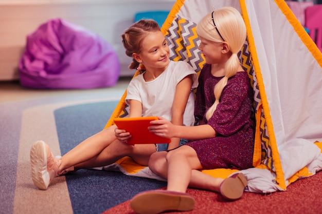 Nasze sekrety. urocza długowłosa dziewczyna z uśmiechem na twarzy, spędzając weekend z koleżanką z klasy