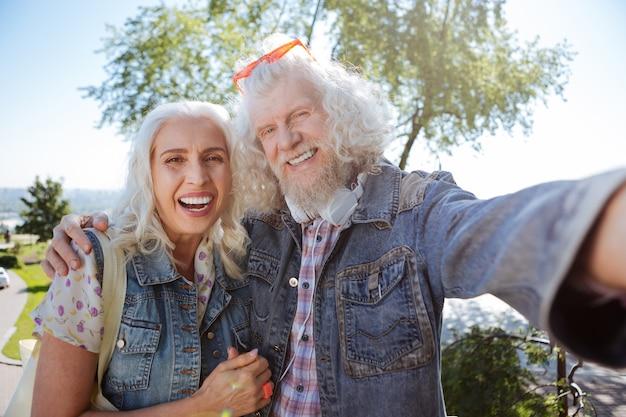 Nasze zdjęcie. szczęśliwa starsza para uśmiecha się podczas wspólnego robienia selfie