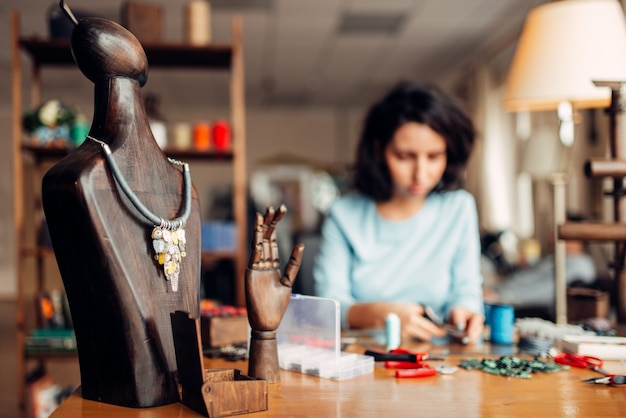 Naszyjnik wykonany ręcznie na drewnianym manekinie, robótki ręczne.