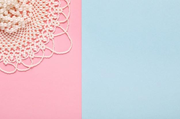 Naszyjnik z białej perły na pastelowym niebieskim i różowym papierze