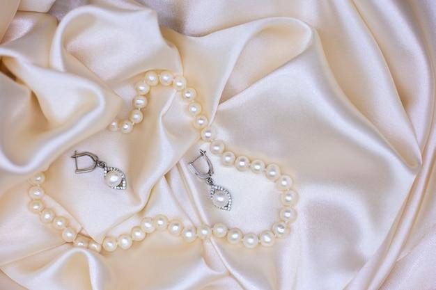 Naszyjnik z pereł i kolczyki z pereł na beżowym jedwabiu widok z góry biżuteria dla panny młodej