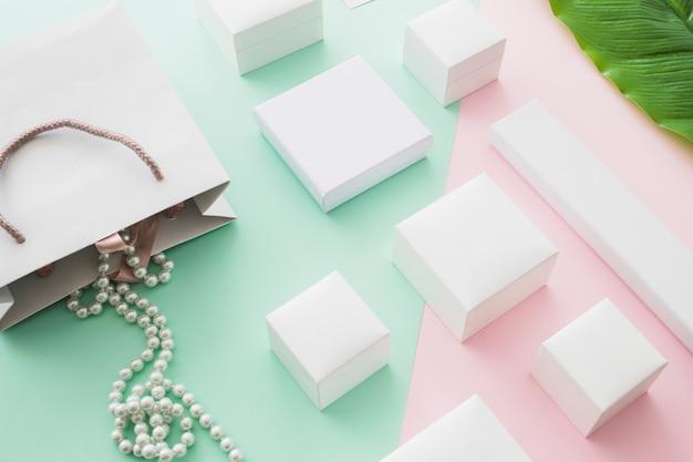 Naszyjnik z pereł spada z torby na zakupy z białymi pudełkami na pastelowym tle