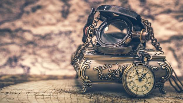 Naszyjnik ze szkła powiększającego i zegarka na mapie