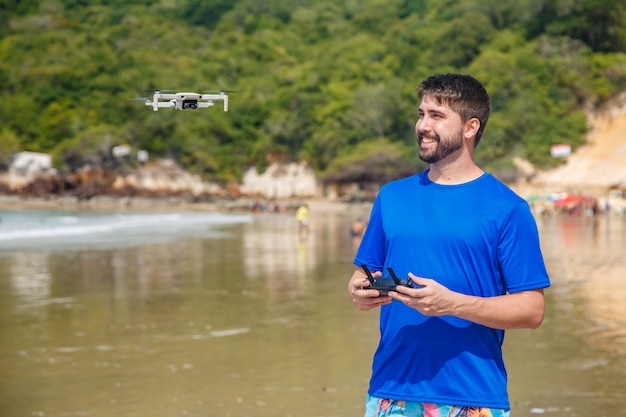 Natal, rio grande do norte, brazylia - 12 marca 2021: człowiek z dronem na plaży morro do careca w natal