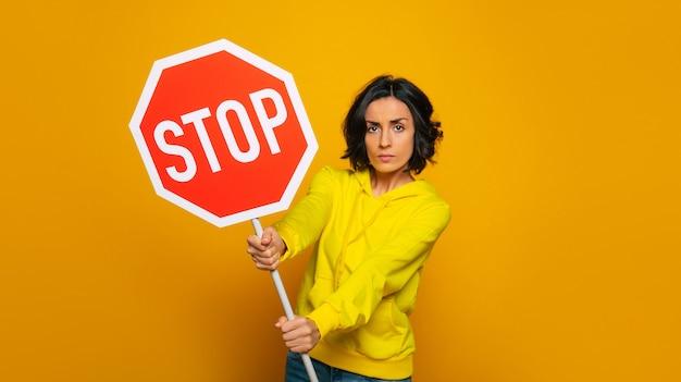 """Natarczywa poważna dziewczyna ubrana w żółtą bluzę z kapturem, zwracająca uwagę na napis """"stop"""" w jej rękach."""