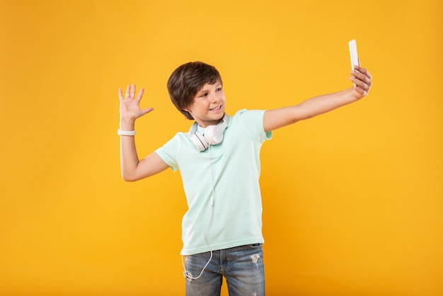 Natchniony. radosny, szczupły chłopiec w słuchawkach i robienia selfie