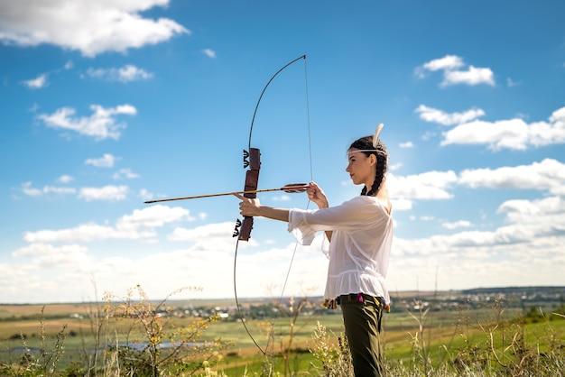 Native american kobieta trzyma łuk i strzały pozowanie w przyrodzie. styl życia