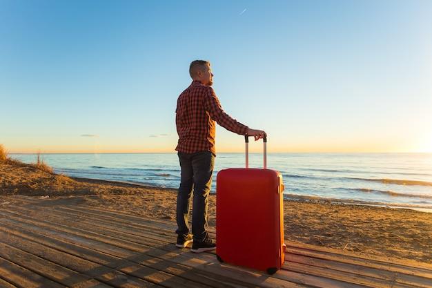 Natura, podróże, koncepcja ludzi - człowiek stojący blisko morza z czerwoną walizką.