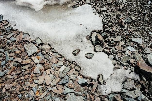 Natura śniegu na chaotycznym stosie kamieni. naturalne tło lodu na losowych głazach. firn na zbliżenie combe rock. widok z góry na śnieżny głaz. minimalistyczna tekstura kamienistego sterty.