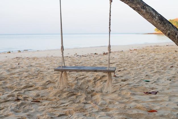 Natura tło huśtawki na palmie kokosowej na wybrzeżu plaży nad morzem na wakacje relaks styl życia koncepcja krajobrazu