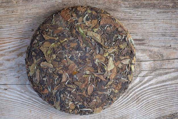 Naturalna chińska biała herbata w formie naleśnika. prasowana okrągła herbata na drewnianym stojaku
