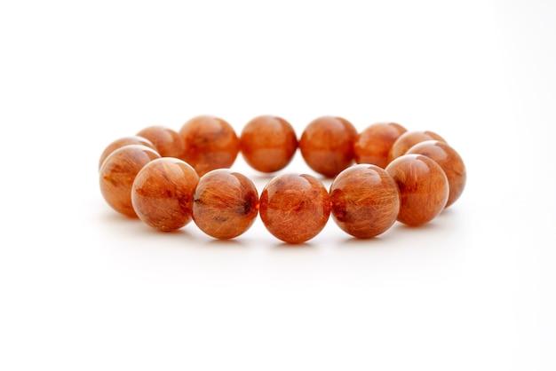Naturalna czerwonawo brązowa bransoletka z kwarcu rutylowego z kamieniami szlachetnymi na białym tle