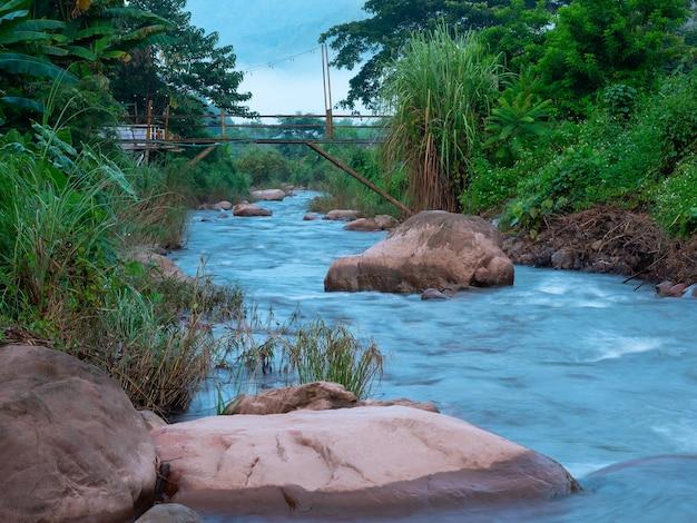 Naturalna czysta świeża woda strumienia w rzece przez duże skały w zielonym lesie z małym drewnianym mostem nad rzeką wczesnym rankiem, cel podróży rzeka mang w wiosce sapan w nan tajlandia