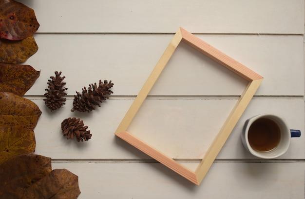 Naturalna drewniana rama i filiżanka herbaty na białym stole szablon tło płasko leżał widok z góry