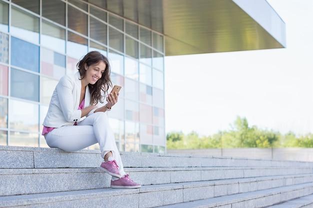 Naturalna dziewczyna uśmiechając się, siedząc na schodach w białym kolorze różowej koszuli i różowych trampkach z luźnymi brązowymi włosami, patrząc na smartfona
