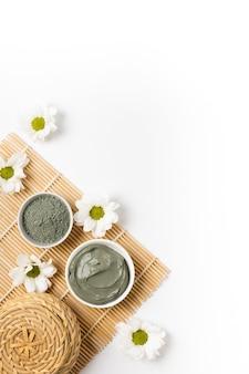 Naturalna glinka kosmetyczna w miseczkach i kwiatami na macie bambusowej do salonu spa