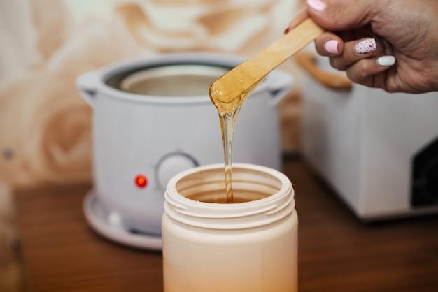 Naturalna gorąca pasta cukrowa do depilacji w słoiku i na drewnianej szpatułce w rękach kosmetyczki