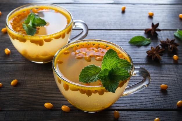 Naturalna jagodowa herbata ze świeżymi jagodami rokitnika i miętą na ciemnym stole