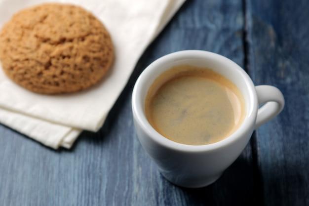 Naturalna kawa espresso w ceramicznej filiżance i ciasteczkach na niebieskim drewnianym stole.