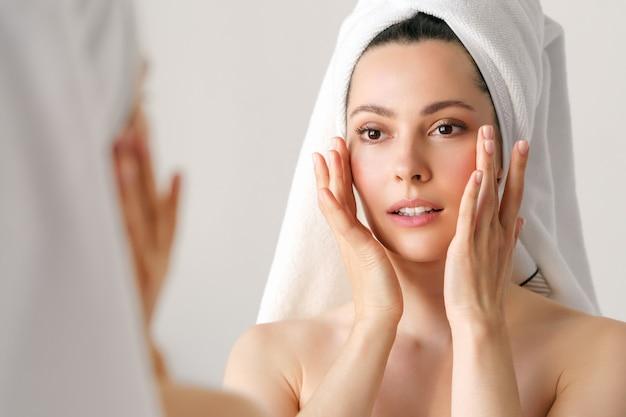 Naturalna kobieta o dobrej skórze trzyma policzki i patrzy w lustro. spa, kosmetologia, uroda.