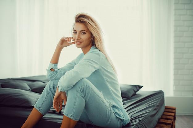Naturalna ładna blondynka siedzi na łóżku
