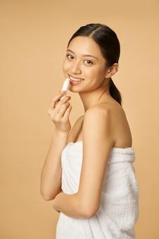 Naturalna młoda kobieta owinięta ręcznikiem uśmiechająca się do kamery, nakładająca balsam do ust podczas pozowania na białym tle