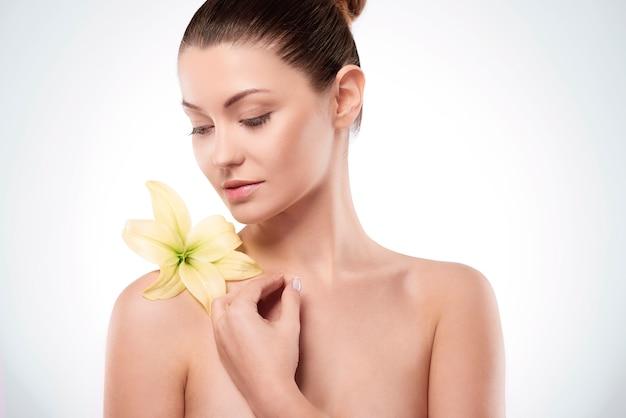 Naturalna młoda kobieta z lilią na ramieniu