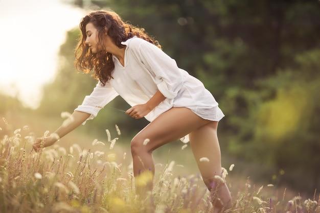 Naturalna piękna dziewczyna wokół kwiatów na świeżym powietrzu w koncepcji przyjemności z wolności