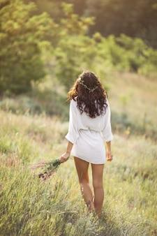 Naturalna piękna dziewczyna z bukietem kwiatów na świeżym powietrzu w koncepcji przyjemności wolności