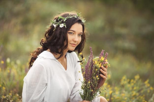 Naturalna piękność dziewczyna z bukietem kwiatów na zewnątrz w wolności koncepcja przyjemności zdjęcie portretowe