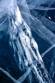 Naturalna tekstura lodu z głębokimi pęknięciami. niebieski przezroczysty lód. pionowy.