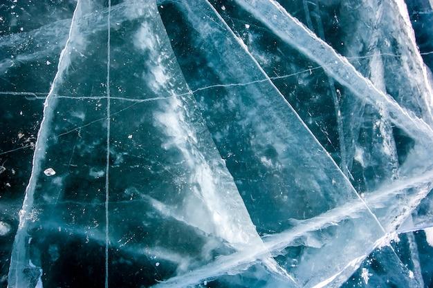 Naturalna tekstura przezroczystego lodu z głębokimi pęknięciami