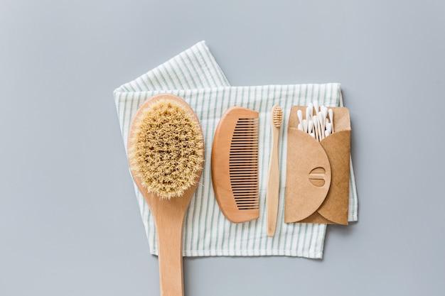 Naturalne akcesoria łazienkowe: drewniany grzebień, bambusowa szczoteczka do zębów, pędzel do masażu, wkładki uszne na szarym tle papieru. zero odpadów.