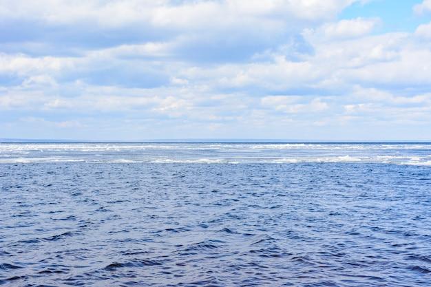 Naturalne bloki lodu rozbijające się o brzeg podczas wiosennej pogody. arktyczny, zimowy, wiosenny krajobraz. lodowy dryf wzdłuż rzeki wołgi.