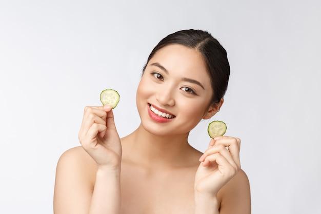 Naturalne domowe świeże ogórki maseczki pod oczy maseczki do twarzy azjatycka kobieta trzyma ogórki i uśmiech relaksuje się z naturalnym domowym