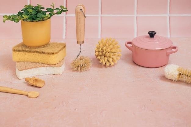 Naturalne ekologiczne bambusowe szczotki do czyszczenia, gąbki, przybory kuchenne, naczynie do zapiekanek i zielona roślina w żółtej doniczce na różowym tle płytek.