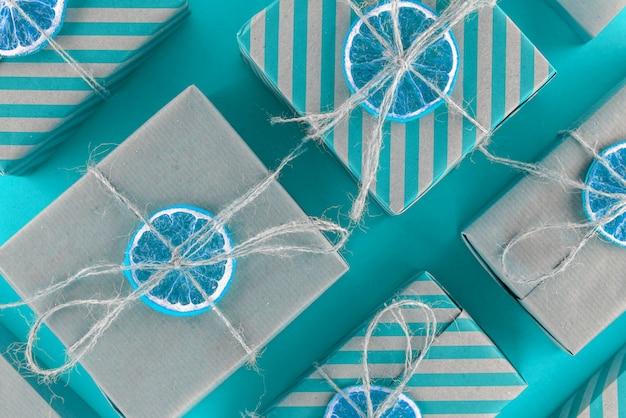 Naturalne i niebieskie paski na prezenty, ozdobione suszoną pomarańczą. ukośne ułożenie pudeł obok siebie.