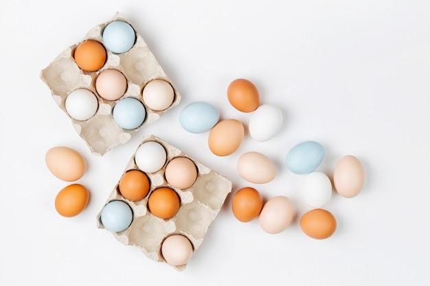 Naturalne kolorowe brązowe i białe jajka w pudełku na jajka. kompozycje w pastelowych kolorach. koncepcja wielkanocy. płaski układanie, widok z góry