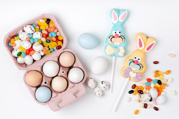 Naturalne kolorowe jajka w polu jajko z jaja wielkanocne cukierki czekoladowe, jellybean i słodki zajączek na białym tle. płaski układanie, widok z góry