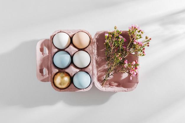 Naturalne kolorowe jajka w pudełku na jajka ozdobione kwiatami w porannym słońcu. stylowe minimalistyczne kompozycje w pastelowych kolorach. koncepcja wielkanocy.