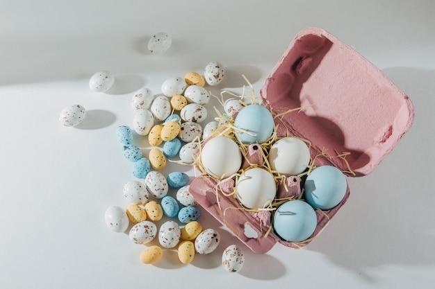 Naturalne kolorowe jajka w pudełku na jajka z cukierkami wielkanocnymi. kompozycje w pastelowych kolorach. koncepcja wielkanocy.