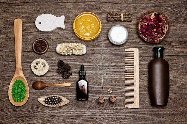 Naturalne kosmetyki do pielęgnacji ciała i włosów na tle drewna produkty spa widok z góry płaska świeca