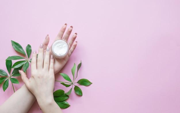 Naturalne kosmetyki do pielęgnacji skóry dłoni z kremową butelką i zieloną rośliną, środkiem zmniejszającym zmarszczki na dłoniach, nawilżającym. piękne kobiety ręce na pastelu.