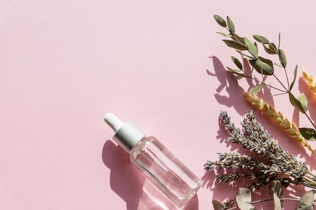 Naturalne kosmetyki z lawendą i pomarańczą, domowe spa na różowej makiecie widok z góry. butelka olejku do masażu lawendy - zabieg kosmetyczny.