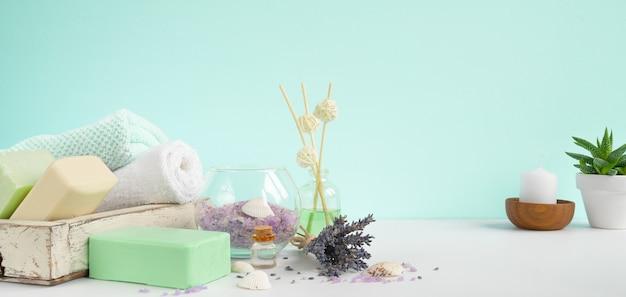 Naturalne mydła do kąpieli do aromaterapii i pielęgnacji ciała. zabieg lawendowy spa, ręczniki, sól morska i suszone zioła. aromaterapia i spa miętowy transparent tło.