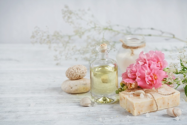 Naturalne mydło ręcznie robione, aromatyczny olej i kwiaty na białym tle drewnianych. koncepcja spa.