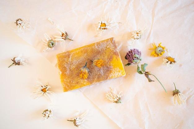 Naturalne mydło ręcznie robione z ekstraktem z kwiatu rumianku. wokół są suszone kwiaty.