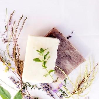 Naturalne mydło z różnymi ziołami, widok z góry, stonowane.